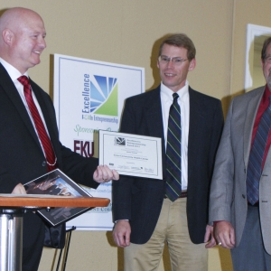 Michael Stanley, left, accepts a framed certificate in recognition of Grace Comm